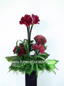 Composizione funebre in vegetazione fiori artificiali